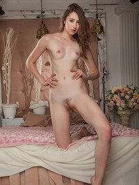 gorgeous Ginger Frost kneels on a bed